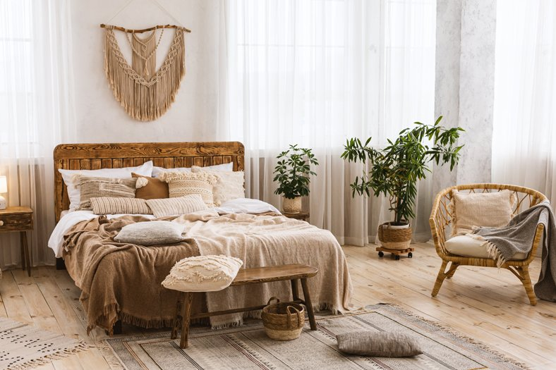 Bedroom interior concept. Cute design with double bed, plants in pots and large windows