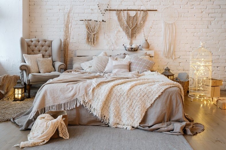 Front view of cozy bedroom with soft plaid and warmth blanket on comfortable bed, pillows, cushions, armchair, home decor and interior design in bohemian style